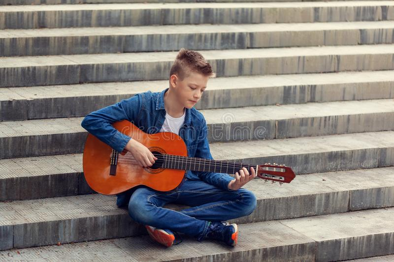Teenager guitar playing sitting on the steps in the park royalty free stock photos