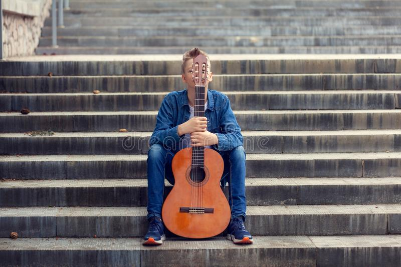 Teenager with guitar sitting on the steps in the park royalty free stock images