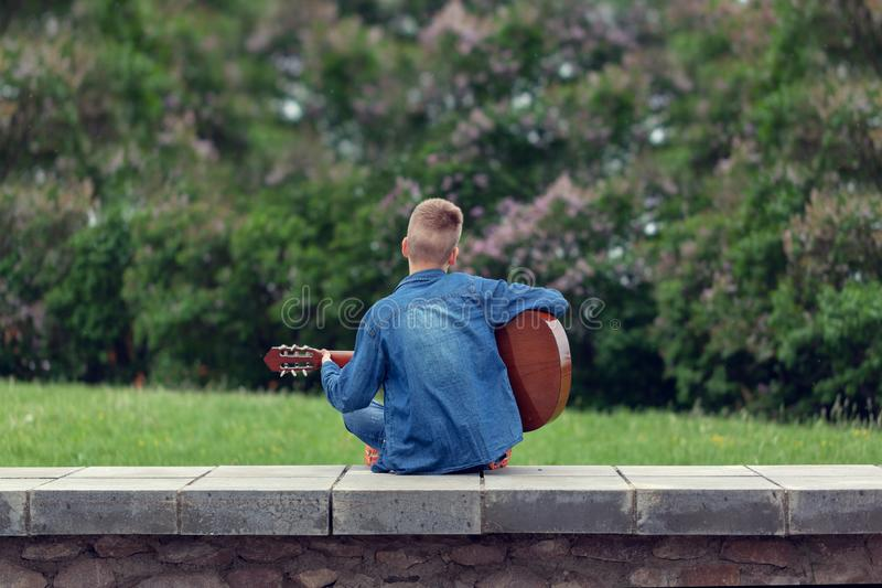 Teenager with guitar sitting on the steps in the park, outdoors. Back view royalty free stock image