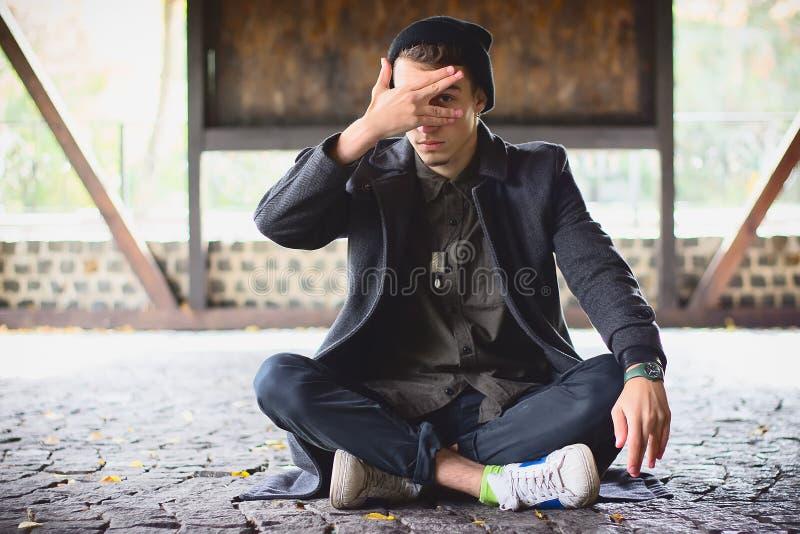 Teenager ha coperto il suo fronte, dante una occhiata tramite le sue dita alla via fotografia stock