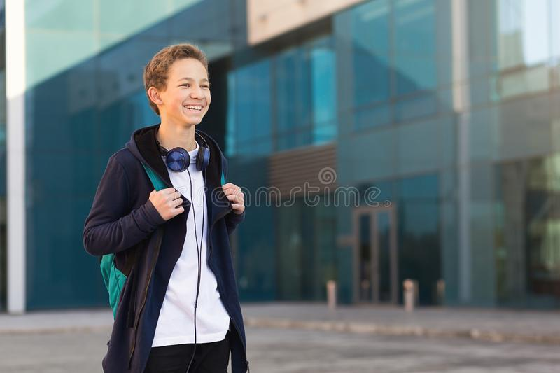 Teenager with headphones and backpack outdoors. Copy space.  royalty free stock photos