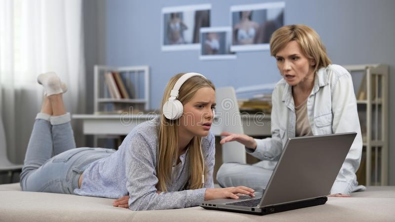 Teenager in headphones ignoring mother, surfing net, difficult puberty age stock photo