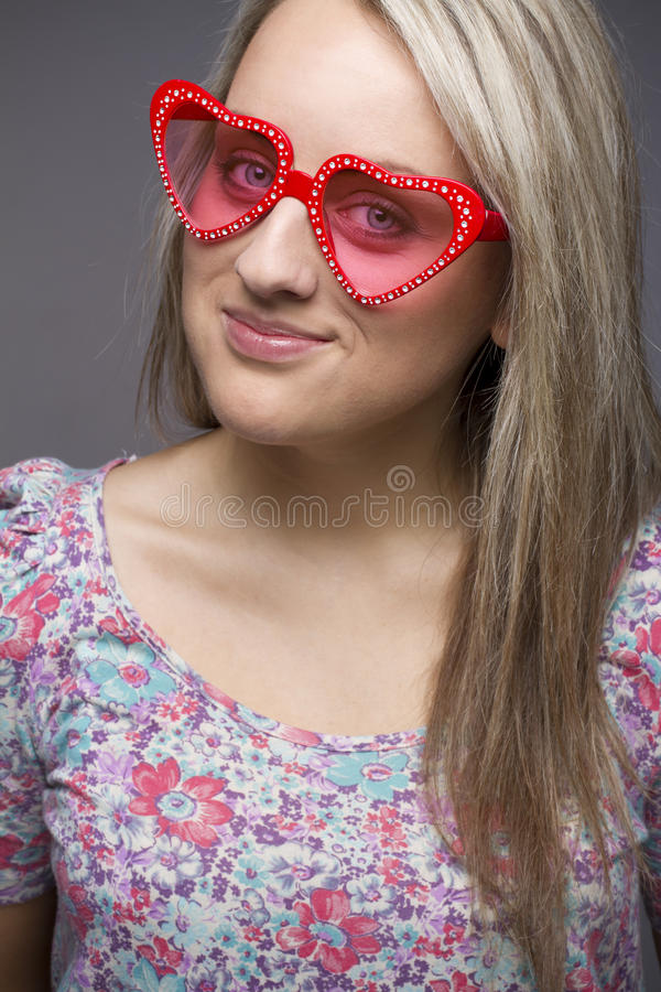 Teenager in heart shape sunglasses stock images