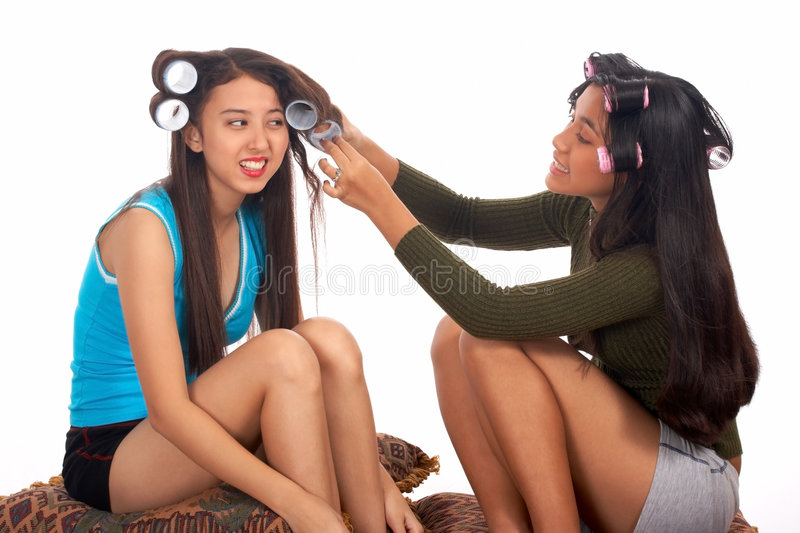 Teenager helping her friend. Removing her hair rollers stock photo