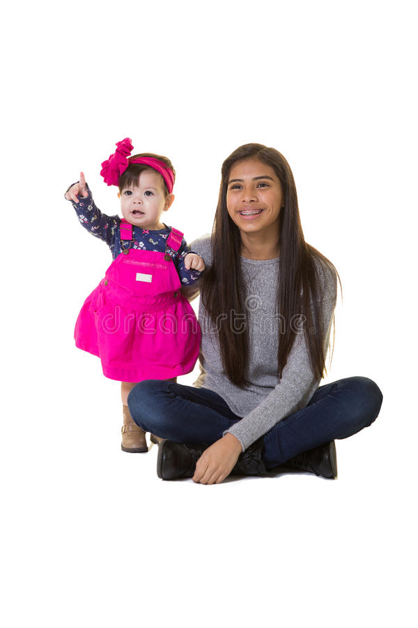 A teenager and her baby sister. Isolated on white stock photography