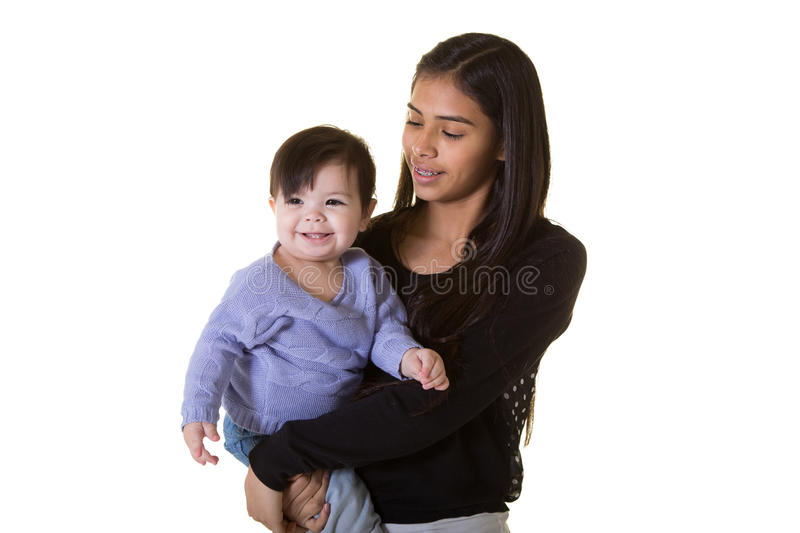 A teenager and her baby sister. Isolated on white stock image