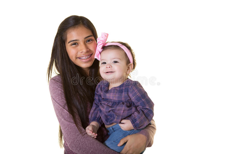 A teenager and her baby sister. Isolated on white royalty free stock photography