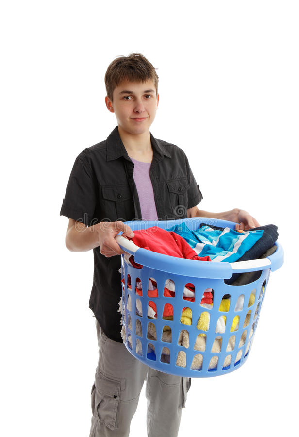 Teenager holding a basket of housework. Boy with a basket full of washing or ironing royalty free stock photography