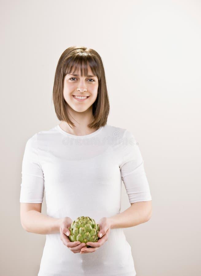 Teenager holding fresh artichoke. Teenager holding wholesome, fresh artichoke stock photos