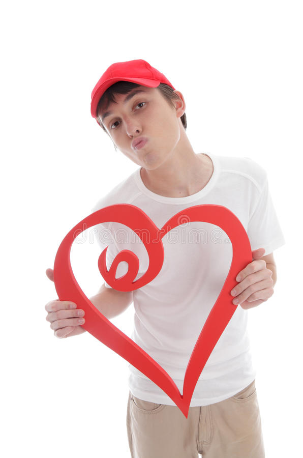 Teenager holding red love heart kiss valentine. A teenage boy holding a red love heart with lips puckered up kissing. White background royalty free stock photography