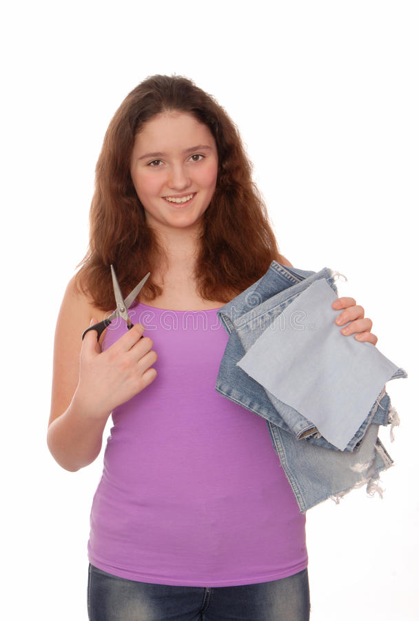 Teenager holds scissors and pieces of jeans. stock image
