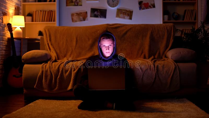 Teenager in hood playing game on laptop or breaking website, cyber attack stock images