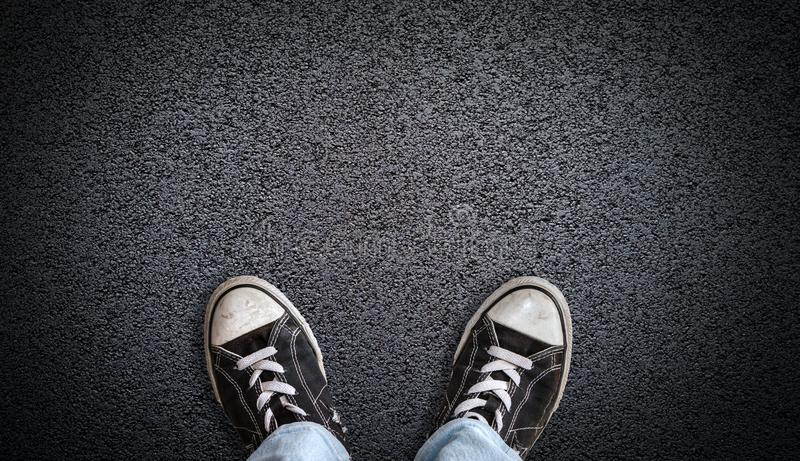Teen wearing canvas shoes on asphalt background with copy space stock images