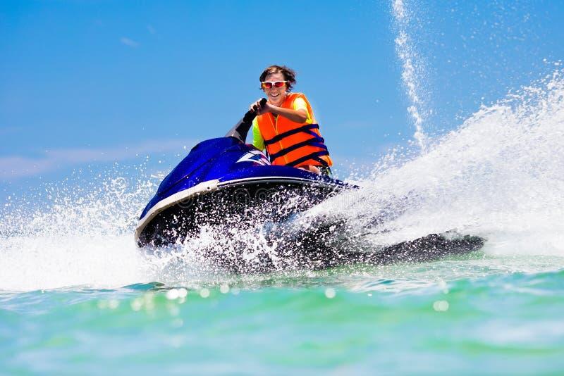 Teenager on jet ski. Teen age boy water skiing. stock photography