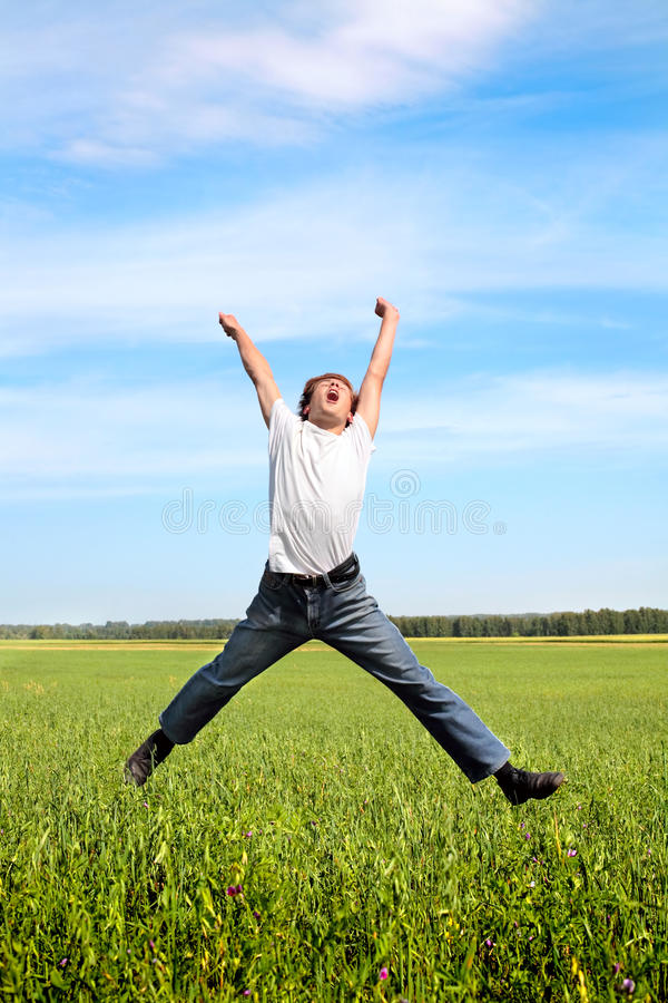 Teenager jumping. Happy teenager jumping on the meadow stock photography