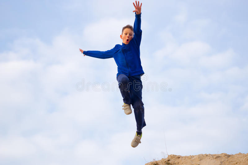 Teenager jumping against the sky. Parkour royalty free stock image