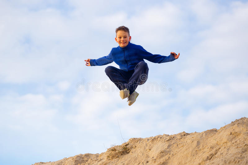 Teenager jumping against the sky. Parkour. On the sand stock photography