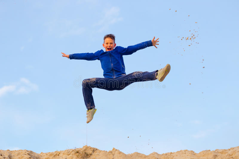 Teenager jumping against the sky. Parkour. On the sand stock photo