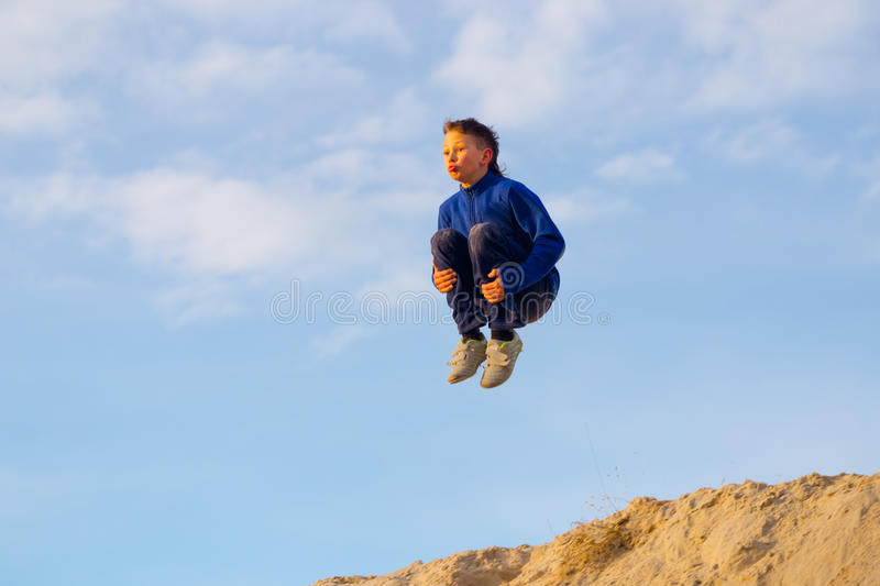 Teenager jumping against the sky. Parkour. On the sand royalty free stock photography