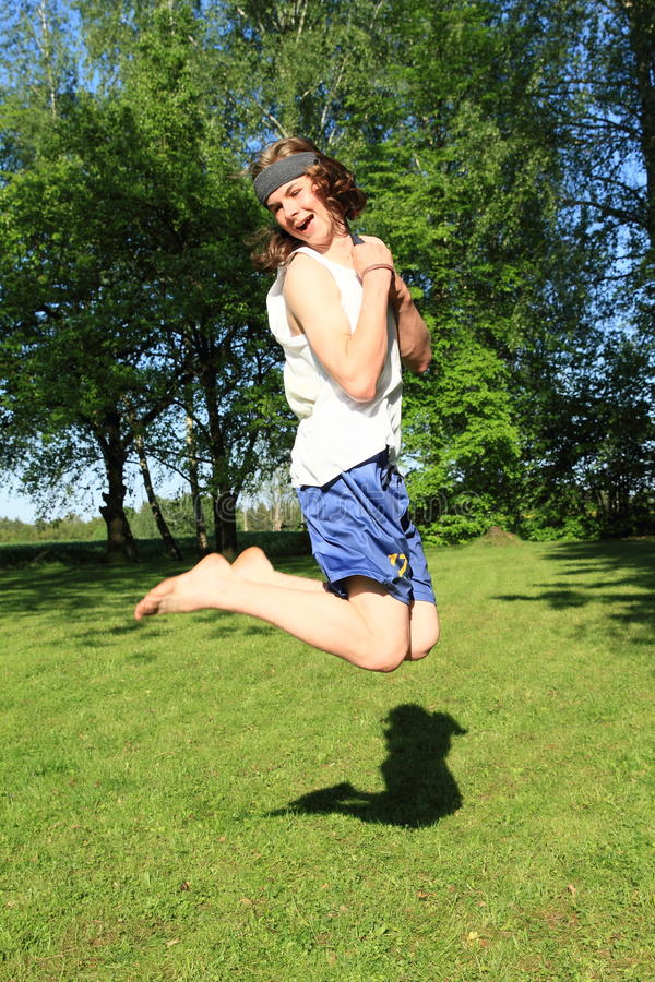 Teenager jumping on meadow. Smiling boy - barefoot teenager dressed in blue shorts and white top jumping on green meadow stock photography