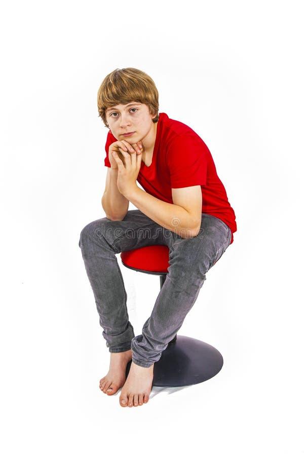 Teenager-Junge sitzt auf einem Hocker stockfotografie