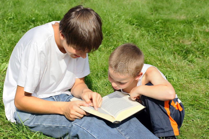 Teenager And Kid With A Book Royalty Free Stock Photo