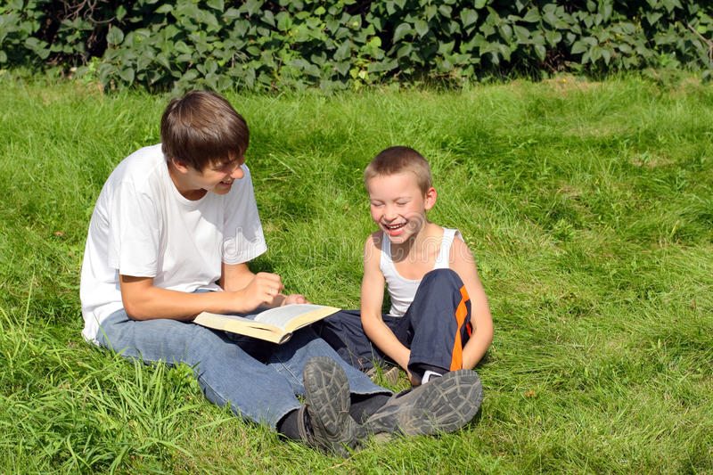 Teenager and kid with a book. The happy teenager and kid with a book on a summer meadow stock photo