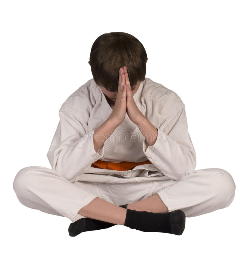 Teenager Kim bowed in training. Teenager sitting in a kimono karate folded his hands together and bowed stock photos