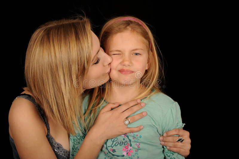 Teenager kissing young sister. Half body portrait of teenager kissing young sister on cheek, isolated on white background stock images