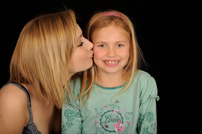 Teenager kissing young sister. Portrait of teenager kissing young sister, black background royalty free stock photo