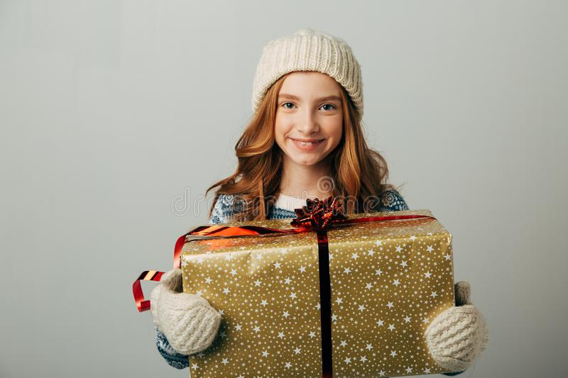 A teenager in a knitted hat, sweater and gloves is smiling. A girl hugs her Christmas present from her parents. She was stock photos