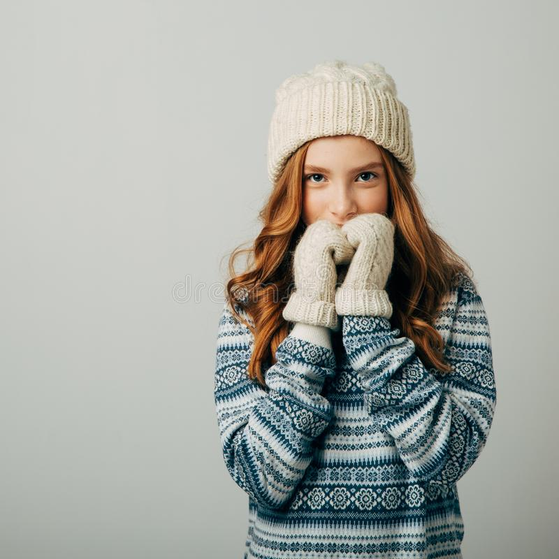 Teenager in a knitted hat, sweater and gloves. She is very warm and comfortable in this dress. The girl is very glad not royalty free stock image