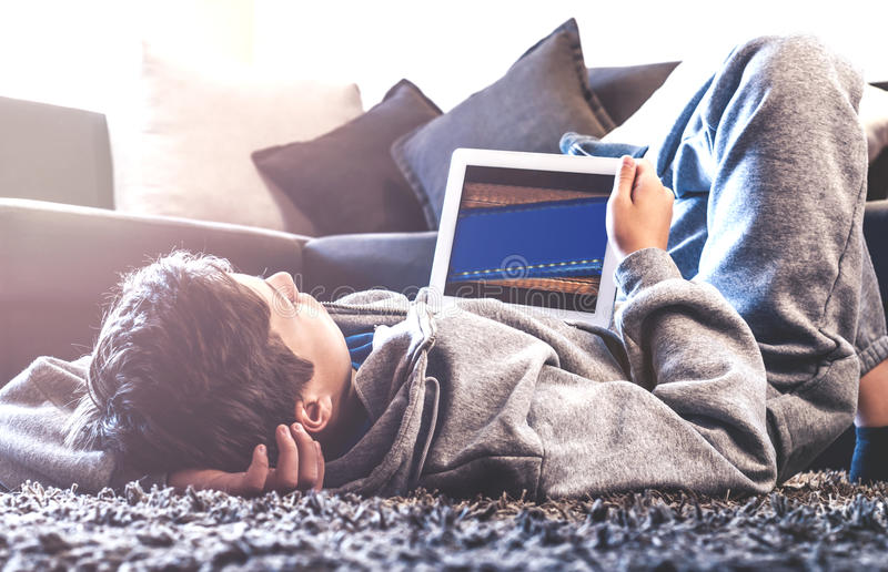 Teenager lay on the floor in the room. Teenager with tablet while lying on the floor in the room stock photography
