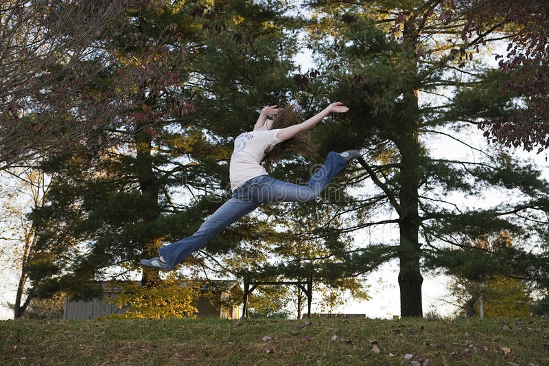 Teenager leaping, jumping. Teenager jumping outside with hands thrown back royalty free stock images