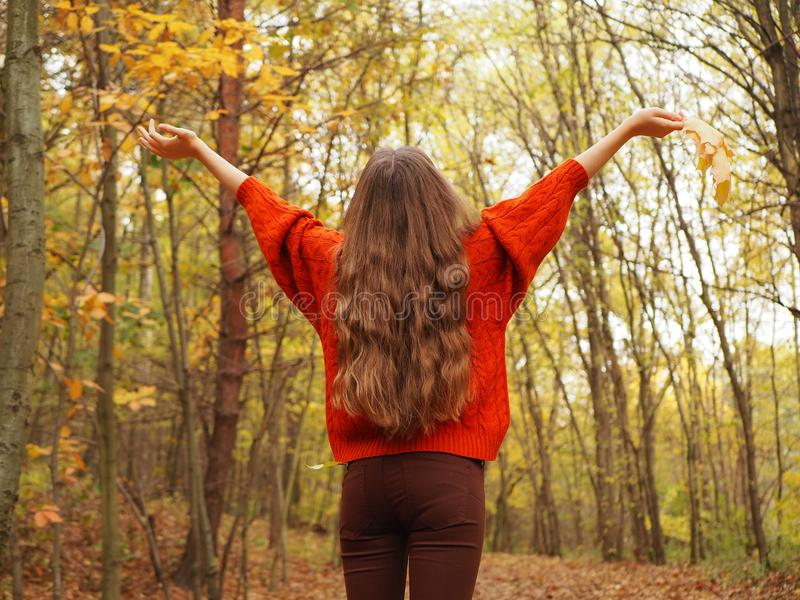 A teenager lifting her hands up with joy. A girl wearing orange sweater and brown jeans stock photo