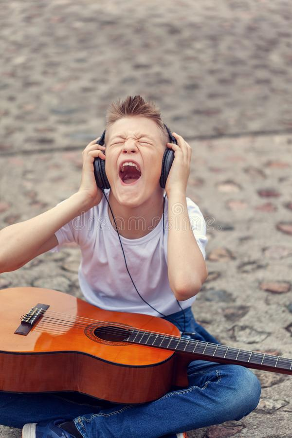 Teenager listening to music on headphones and screaming song. Young man sitting with a guitar on the street stock photography