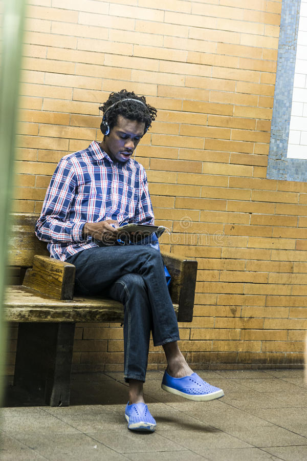 Teenager listens to music while waiting at subway station stock photo