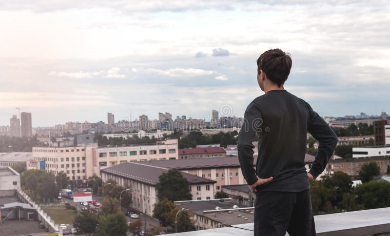 Teenager is looking off into the distance while standing on the. Teen looks into the distance, standing on the edge of the rooftop stock photography