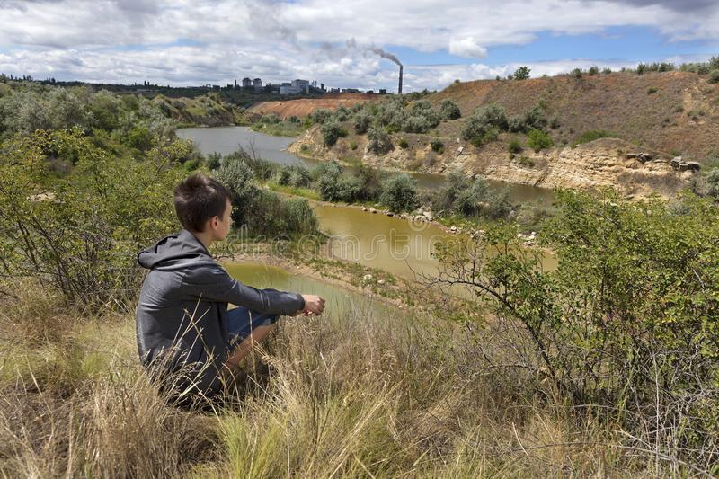 A teenager looks at the landscape of an abandoned sandy quarry on a summer day. stock photography