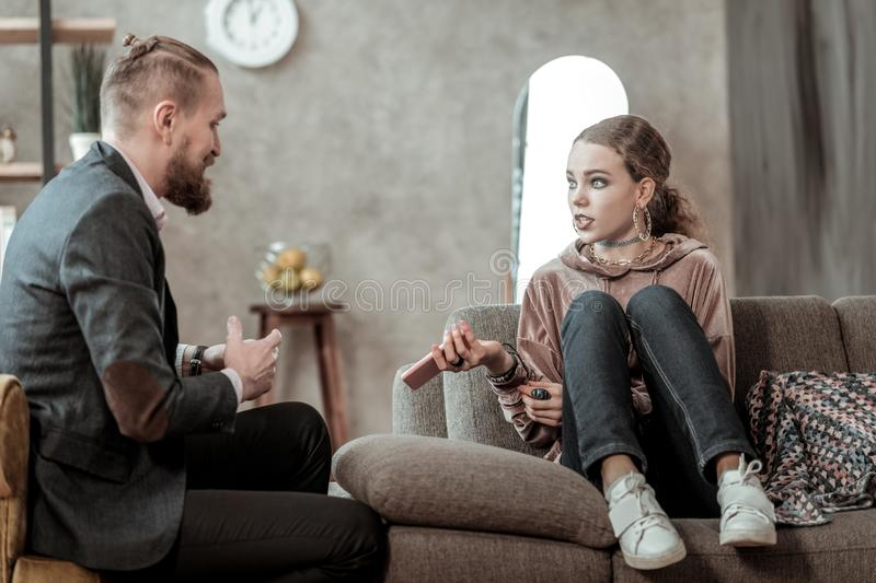 Teenager with makeup having emotional talk with counselor. Emotional talk. Stylish teenage girl with dark makeup having emotional talk with counselor royalty free stock photos