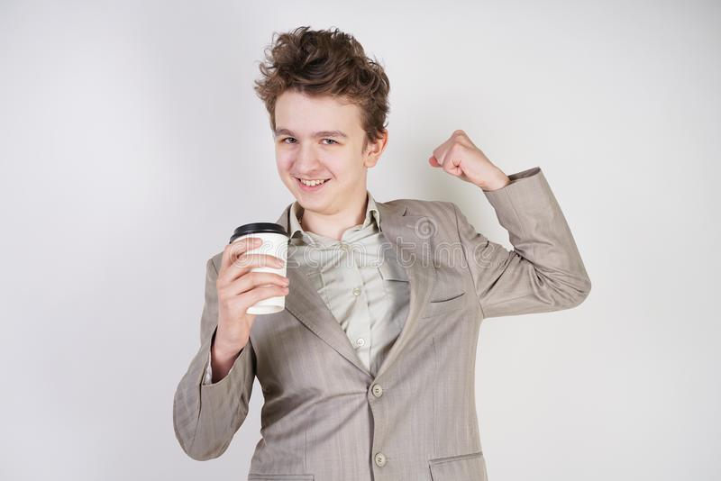 Teenager male in gray business suit with paper Cup of coffee in hand on white studio background royalty free stock photography