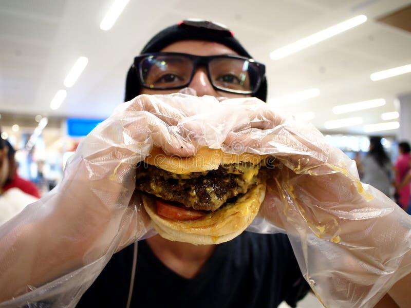 Teenager mangiando un grande hamburger immagine stock