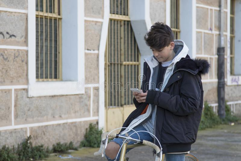 Teenager with mobile phone and vintage bike. On urban street royalty free stock photography