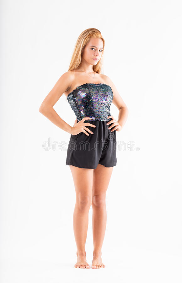 Teenager model with arms akimbo. Teenager model with her arms akimbo on a white background with a challenging sly and smart expression royalty free stock photography