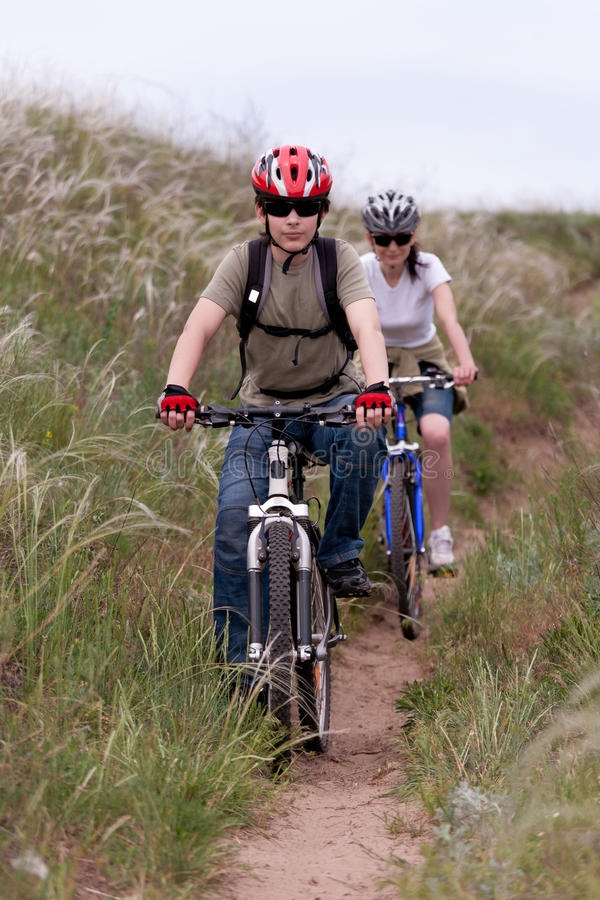 Teenager on the mountain bike. Teenager and young woman on the mountain bike royalty free stock image