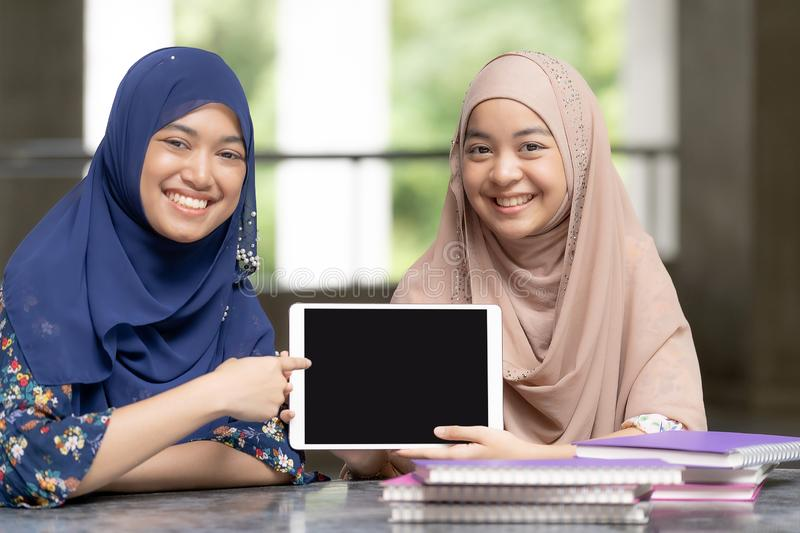 Teenager muslim students with tablet royalty free stock photo