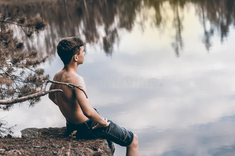 Teenager near the lake sits on a rock. Teenager has a rest near the lake sits on a rock stock photos