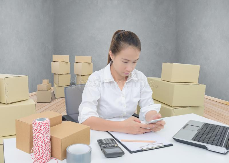 Teenager owner business woman work at home with smartphone, laptop for online shopping writing the order. Teenager owner business woman work at home or office royalty free stock images