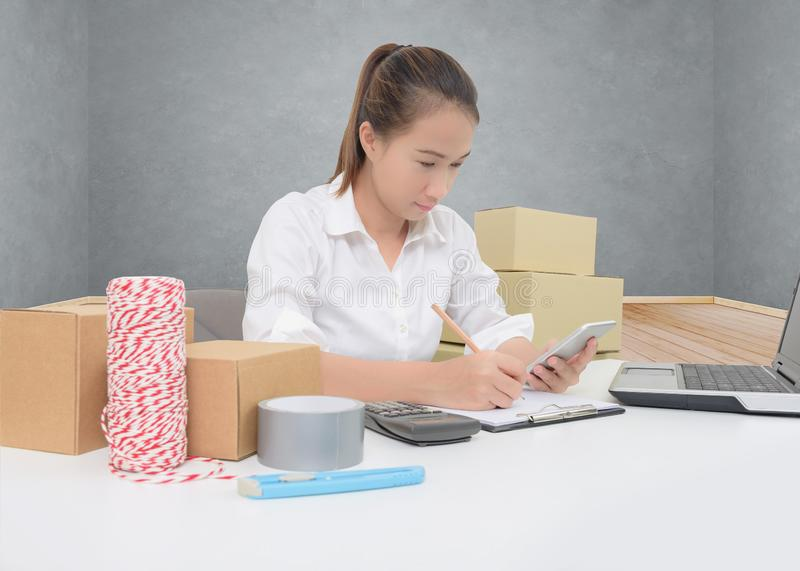Teenager owner business woman work at home with smartphone, laptop for online shopping writing the order. Teenager owner business woman work at home or office stock images