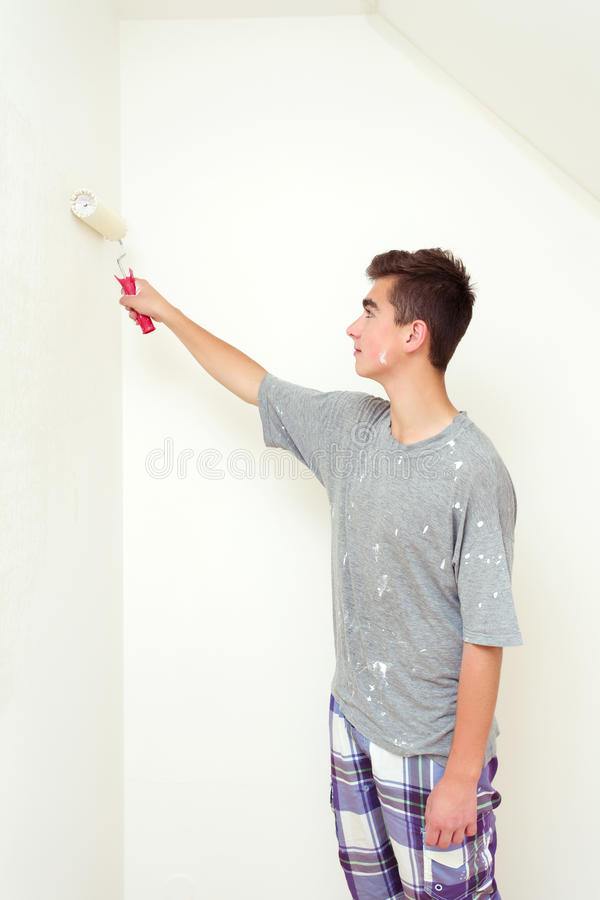 Teenager painting wall to white at home royalty free stock image